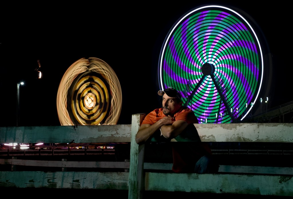 Justin Cole, 32, of Waynesboro,  watches the rides along the midway the Ferris  wheel and Zipper ride spin in the background at the Shenandoah County Fairground